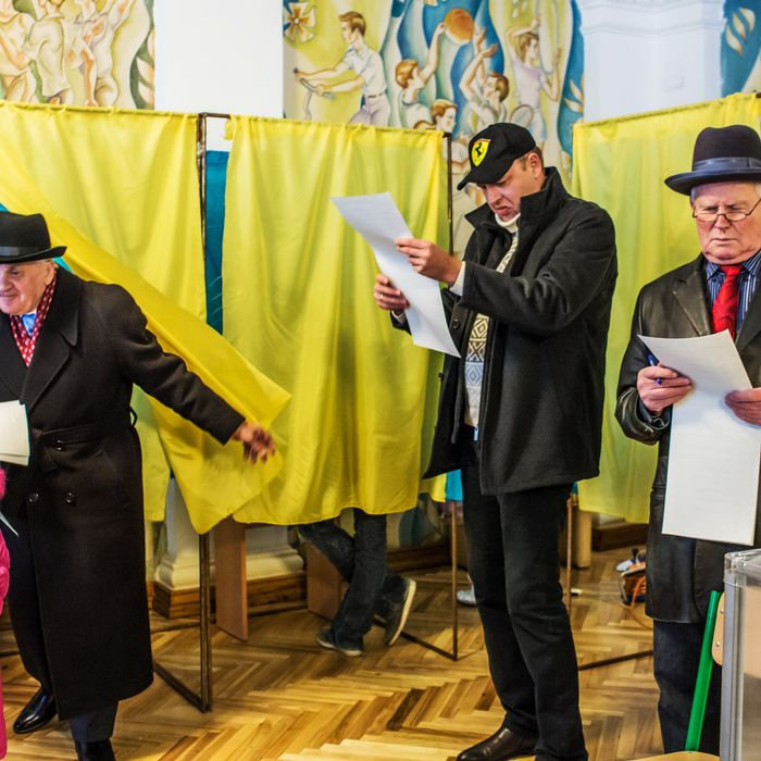 Voters review their ballots before casting their votes in parliamentary elections at a polling station on October 26, 2014 in Kiev, Ukraine. Although a low turnout is expected in the east of the country amid continued fighting between Ukrainian forces and pro-Russian separatists, Ukraine is expected to elect a pro-Western parliament in a further move away from Russian influence.