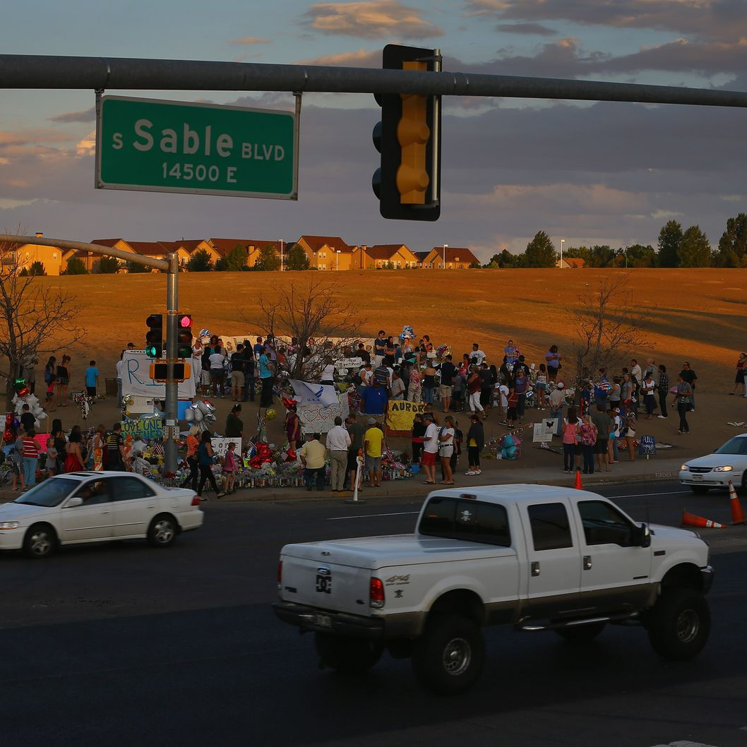 AURORA, CO - JULY 26:  People visit a memorial setup across the street from the Century 16 movie theatre where James Holmes is suspected of a mass shooting on July 26, 2012 in Aurora, Colorado. Twenty-four-year-old James Holmes is suspected of killing 12 and injuring 58 others Friday during a shooting rampage at a screening of 'The Dark Knight Rises.'  (Photo by Joe Raedle/Getty Images)