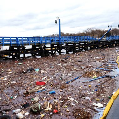 November 01,2012.Workman setup a fuel containment barrier by orders of the U.S. Coast Guard. Hurricane Sandy turned over boats that spilled diesel fuel in Sheepshead Bay.Debris and diesel fuel mix together in Sheepshead Bay.