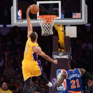Xavier Henry #7 of the Los Angeles Lakers attempts a dunk while being pursued by Iman Shumpert #21 of the New York Knicks at STAPLES Center on March 25, 2014 in Los Angeles, California.