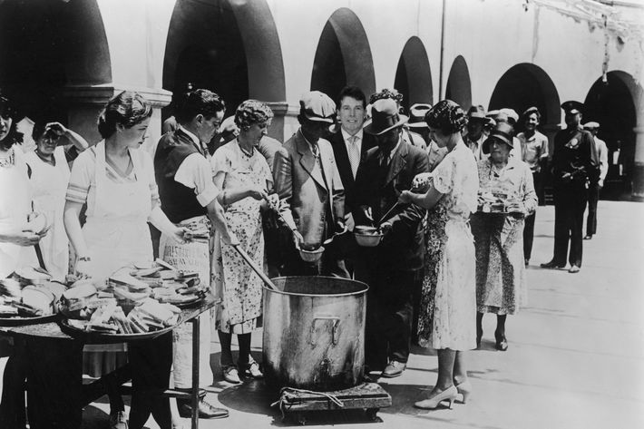 1930: Unemployed men receiving soup and slices of bread in an outdoor breadline during the Great Depression, Los Angeles, California. Some women serve the soup with large ladles while others hand out slices of bread from trays. (Photo by American Stock/Getty Images)