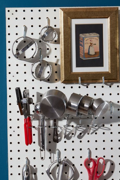 A pegboard with measuring cups, kitchenware, and a print hanging on it