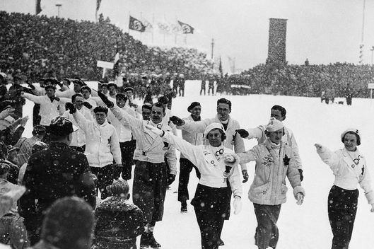 17 Dec 1936, Germany --- Original caption: 12/17/1936-Garmisch Partenkirschen, Germany- Members of the Canadian Winter Olympics team return a Nazi salute, as they pass the reviewing stand in the parade opening the 1936 Winter Olympic Games. --- Image by ? Bettmann/CORBIS