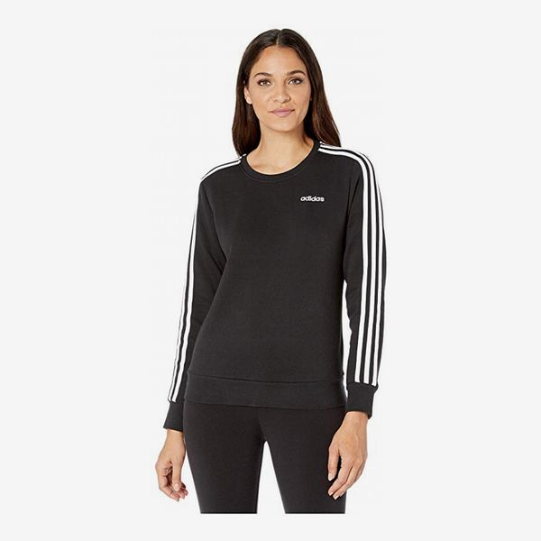 A classic adidas Essential black fleece crew sweatshirt with the Adidas logo and 3 Stripes down the arms and black leggings on a model.