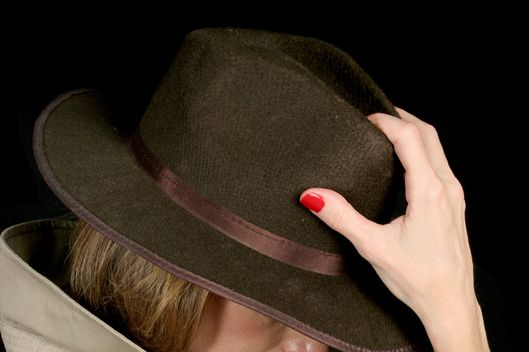 A beautiful, mysterious woman in a trenchcoat and fedora hat, turned away so her face is hidden.
