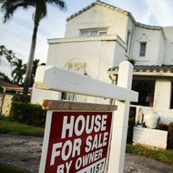A 'For Sale' sign is posted in front of a house in Hollywood, Florida.