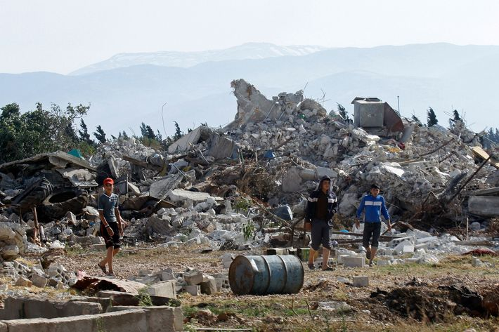 Syrian youths walk amongst the rubble in the village of al-Hamidiyeh, north of Qusayr, in Syria's central Homs province on June 7, 2013 as regime forces sought to mop up the final pockets of rebel resistance north of Qusayr, after retaking the key town that was an insurgent bastion for a year, a watchdog said. Qusayr's capture gives President Bashar al-Assad the upper hand if a US-Russian plan for the first direct peace talks with his opponents materialises, analysts say.