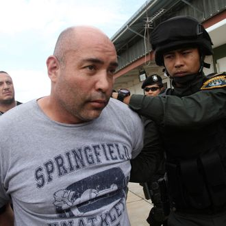 Joseph Manuel Hunter, left, is led by Thai police commandos to Police Aviation Division after being arrested, in Bangkok, Thailand, Thursday, Sept. 26, 2013. Thai police said they arrested the American man wanted by the U.S. for allegedly running a drug trafficking network that spanned Asia and the United States. Hunter was arrested Wednesday on the resort island of Phuket as part of a sting operation launched at the request of the U.S. Drug Enforcement Agency. (AP Photo/Sakchai Lalit)