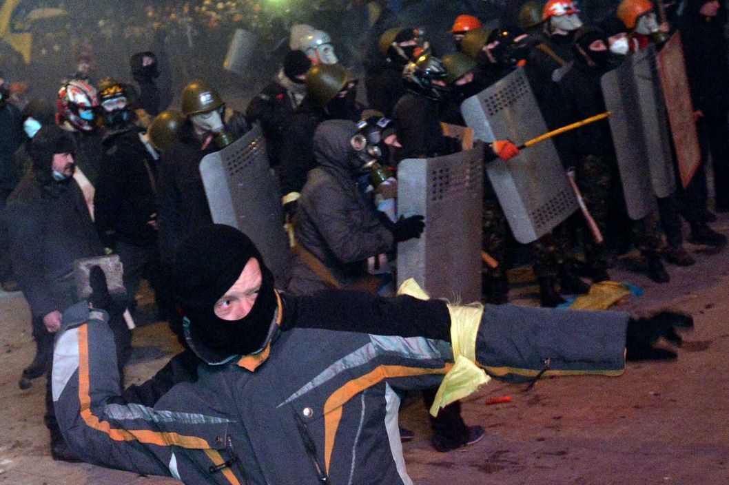 A protester prepares to throw a brick as protesters clash with police during an opposition rally on January 19, 2014 in the centre of the Ukrainian capital Kiev in a show of defiance against strict new curbs on protests. 200,000 protesters expressed frustration over the lack of a clear programme from the opposition leaders after almost two months of protests over the government's ditching of a pact with the EU under Russian pressure. AFP PHOTO / SERGEI SUPINSKY        (Photo credit should read SERGEI SUPINSKY/AFP/Getty Images)
