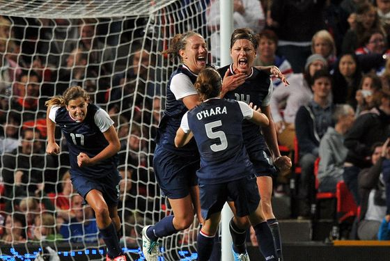US forward Abby Wambach (L) celebrates scoring a penalty during the London 2012 Olympic women's football semi final match between the US and Canada at Old Trafford in Manchester, north-west England, on August 6, 2012.  AFP PHOTO/PAUL ELLIS        (Photo credit should read PAUL ELLIS/AFP/GettyImages)