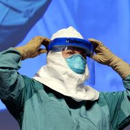 Barbara Smith, RN,(screen-R) Mount Sinai Health Sysytems demonstrates the proper technique for donning and removing protective gear during an ebola educational session for healthcare workers at the Jacob Javits Center in New York on October 21, 2014.  AFP PHOTO / Timothy A. Clary        (Photo credit should read TIMOTHY A. CLARY/AFP/Getty Images)