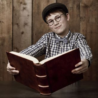 Young boy in retro clothing wearing spectacles holding a massive book --- Image by ? 13/PeopleImages.com/Ocean/Corbis