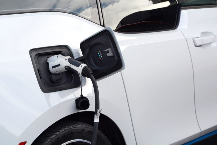 A photo of a white electric vehicle with a charger plugged in.
