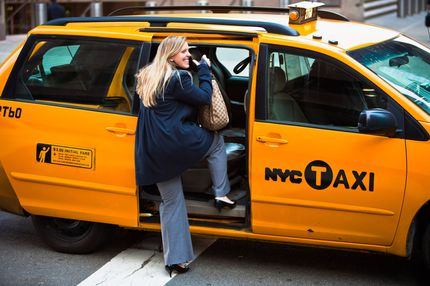 A woman is hailing a yellow cab on Lower Manhatten on March 10, 2010 in New York, New York.