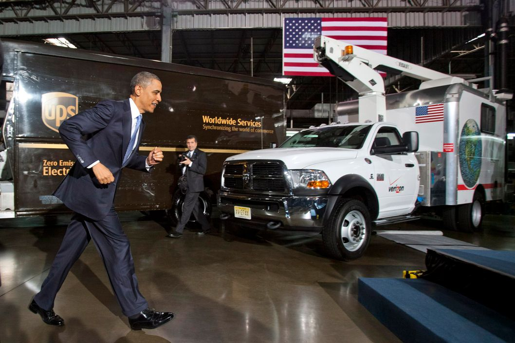 U.S. President Barack Obama jogs to the podium to address United Parcel Service Inc. (UPS) employees after inspecting AT&T Inc., FedEx Corp., PepsiCo Inc., Verizon Communications Inc. and UPS clean fleet vehicles at a shipping facility in Landover, Maryland, U.S., on Friday, April 1, 2011. President Barack Obama spoke about the U.S. employment report for March, the outlook for his administration and Congress to reach a budget agreement, and a partnership between government and companies to help reduce the nation's dependence on foreign oil and spur job growth.