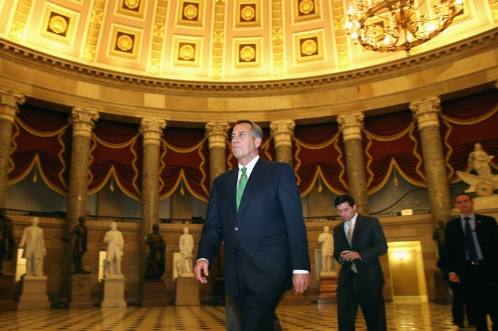 "Speaker of the House John Boehner (R-OH) (C) walks through Statuary Hall before entering the House Chamber to oversee a vote on ""fiscal cliff"" legislation during a rare New Year's Day session  January 1, 2013 in Washington, DC. The House is set to vote up-or-down on a negotiated bill to avert the ""fiscal cliff"" that passed the Senate in the early hours Tuesday."