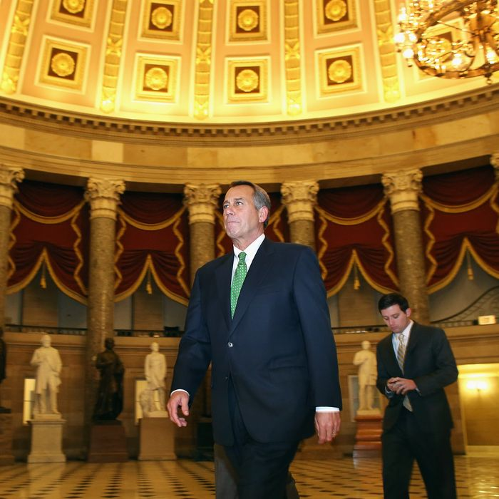 Speaker of the House John Boehner (R-OH) (C) walks through Statuary Hall before entering the House Chamber to oversee a vote on