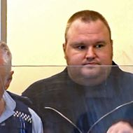 "This TV grab shows Internet guru and founder of Megaupload.com, Kim Schmitz, also known as ""Kim Dotcom"",  escorted by a policeman as he appears in an Auckland district court in New Zealand on January 20, 2012."