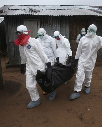 A Liberian burial team wearing protective clothing retrieves the body of a 60-year-old Ebola victim from his home on August 17, 2014 near Monrovia, Liberia. The epidemic has killed more than 1,000 people in four African countries, and Liberia now has had more deaths than any other country.