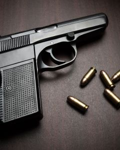 handgun with bullets on the wooden surface, closeup with vignette, useful for various security,protection or criminal topics