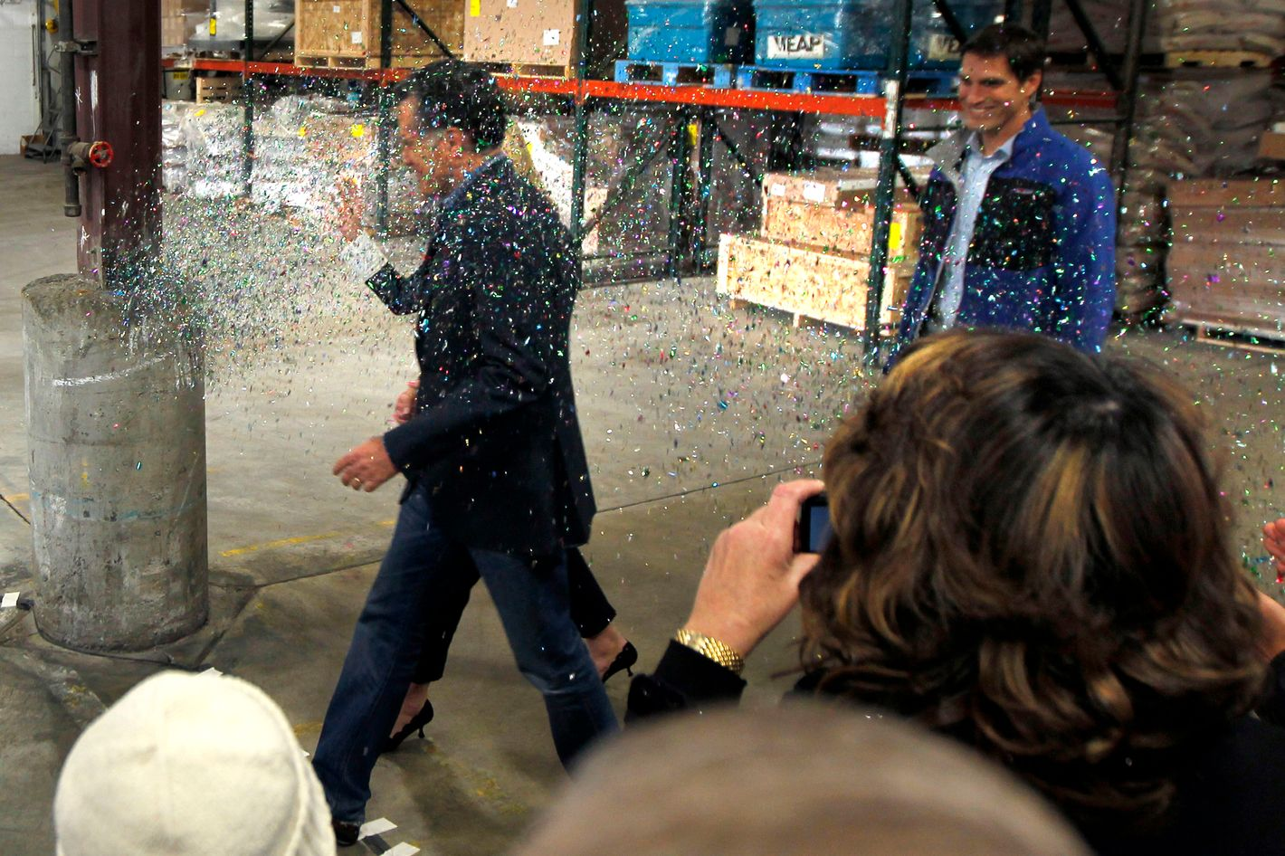 A gay rights activist, not pictured, throws a cup of glitter on Republican presidential candidate, former Massachusetts Gov. Mitt Romney as he walks to the stage at the start of a campaign rally in Eagan, Minn., Wednesday, Feb. 1, 2012. (AP Photo/Gerald Herbert)