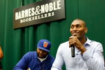 "Heddrick McBride (L) and NBA player Metta World Peace sign copies of their children's book ""Metta's Bedtime Stories"" at Barnes & Noble Tribeca on September 18, 2013 in New York City."