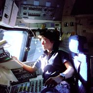 American astronaut Sally K. Ride, mission specialist on STS-7, monitors control  panels from the pilot's chair on the Flight Deck. Floating in front of her is a flight procedures notebook june 25, 1983.