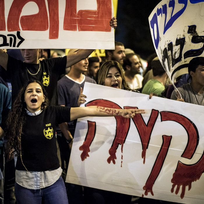 Right wing activist hold signs calling for revenge during a protest on October 23, 2014 in Jerusalem, Israel. The protest took place at the site of the terror attack.