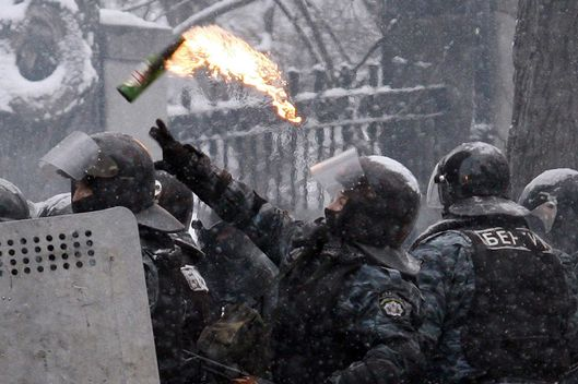 A Ukrainian police officer throws a Molotov cocktail during clashes with protesters in the centre of Kiev on January 22, 2014. Ukrainian police today stormed protesters' barricades in Kiev as violent clashes erupted and activists said that one person had been shot dead by the security forces. Total of two activists shot dead during clashing. The move by police increased tensions to a new peak after two months of protests over President Viktor Yanukovych's failure to sign a deal for closer ties with the EU. AFP PHOTO/ YURIY KIRNICHNY        (Photo credit should read YURIY KIRNICHNY/AFP/Getty Images)