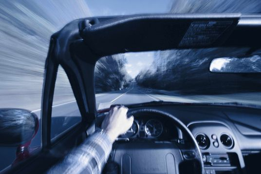 Man driving convertible sports car (blurred motion)