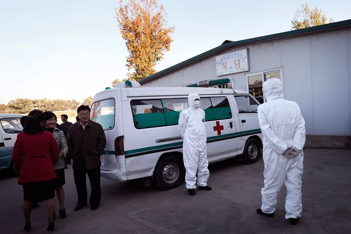 27 Oct 2014, Pyongyang, North Korea --- Medical staff are dressed in protective suits as they wait by an ambulance, at the Sunan International Airport, Monday, Oct. 27, 2014 in Pyongyang, North Korea. North Korea last week stepped up its measures to prevent the spread of the Ebola virus while a major travel agency that specializes in tours to the reclusive country said it had been informed Pyongyang may ban foreign tourists from visiting.(AP Photo/Wong Maye-E) --- Image by ? Wong Maye-E/AP/Corbis