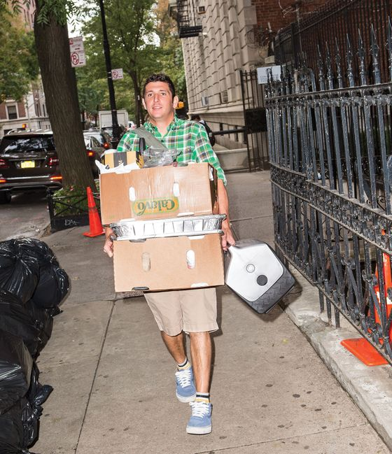 Saffer carrying boxes of supplies, plus a cooler to hold the oysters.