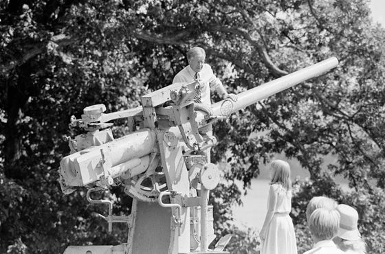 U.S. President Jimmy Carter reaches for the barrel of on old Navy gun that overlooks the Mississippi River in Burlington, Iowa's Crapo Park, Wednesday, August 22, 1979. Daughter Amy looks and listens. (AP Photo/Thumma)
