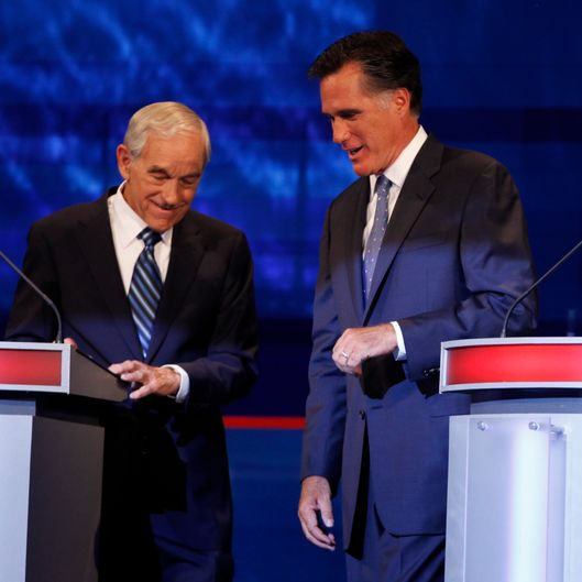 AMES, IA - AUGUST 11:  Republican presidential candidates former Massachusetts Gov. Mitt Romney and Rep. Ron Paul, R-Texas talk during a commercial break at the Iowa GOP/Fox News Debate on August 11, 2011 at the CY Stephens Auditorium in Ames, Iowa. This is the first Republican presidential debate in the state ahead of Saturday's all important Iowa Straw Poll. (Charlie Neibergall-Pool/Getty Images)