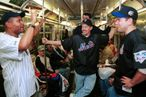 "380625 03: On the eve of the first New York ""Subway Series"" in 44 years, Yankees and Mets fans exchange words on the number 4 subway train October 21, 2000 en route to Yankee Stadium in the Bronx in New York City. The Yankees play the New York Mets as baseball's World Series opens at Yankee Stadium. (Photo by Spencer Platt/Newsmakers)"