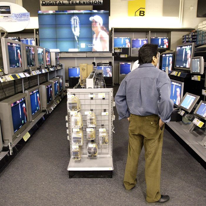 A shopper looks at televisions at Best Buy April 1, 2003 in Chicago. Best Buy announced lower fourth quarter earnings earlier in the day and cut first quarter projections.