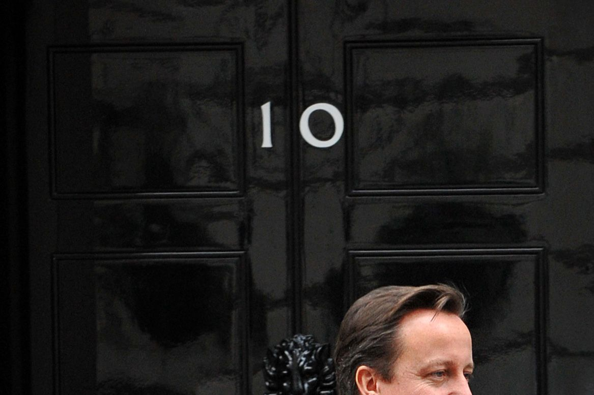 """British Prime Minister David Cameron is pictured at the front door of 10 Downing Street in London, on November 16, 2011, as he awaits the arrival of Serbian President Boris Tadic. The Bank of England on Wednesday cut its forecasts for British economic growth, saying the """"single biggest risk"""" comes from the eurozone debt crisis. Gross domestic product (GDP) is expected to grow by no more than 1.0 percent in 2011 and 2012, compared with the previous guidance for growth of about 1.4 percent and 2.0 percent respectively, the bank said in a quarterly report. AFP PHOTO/BEN STANSALL (Photo credit should read BEN STANSALL/AFP/Getty Images)"""