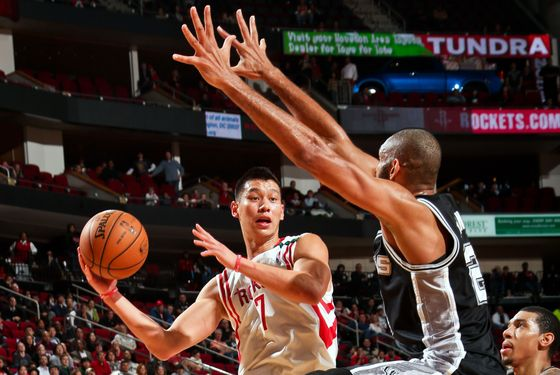 Jeremy Lin #7 of the Houston Rockets looks to pass the ball against Tim Duncan #21 of the San Antonio Spurs on December 10, 2012 at the Toyota Center in Houston, Texas.