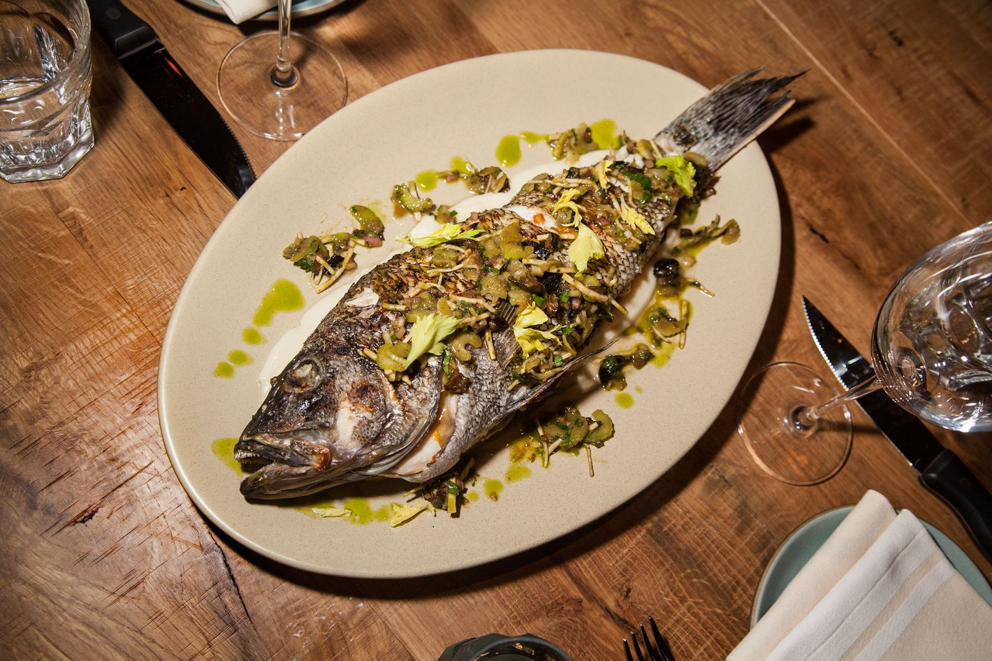 Whole roasted black sea bass is cooked on a wood grill.