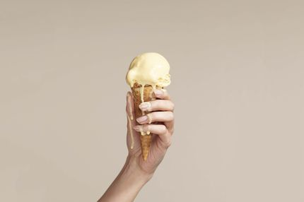 Woman holding melting ice cream cone .