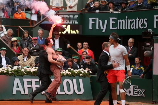 PARIS, FRANCE - JUNE 09: Rafael Nadal of Spain looks on as security guards restrain a protester after he lit a flare and ran on court before the start of a game in the Men's Singles final match between Rafael Nadal of Spain and David Ferrer of Spain during day fifteen of the French Open at Roland Garros on June 9, 2013 in Paris, France.  (Photo by Matthew Stockman/Getty Images)
