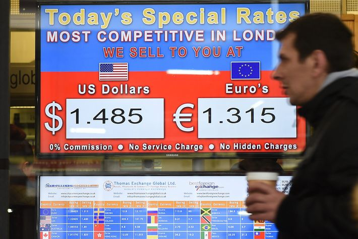 A pedestrian passes a euro dollar currency exchange rate screen in London, Britain, 26 January 2015.