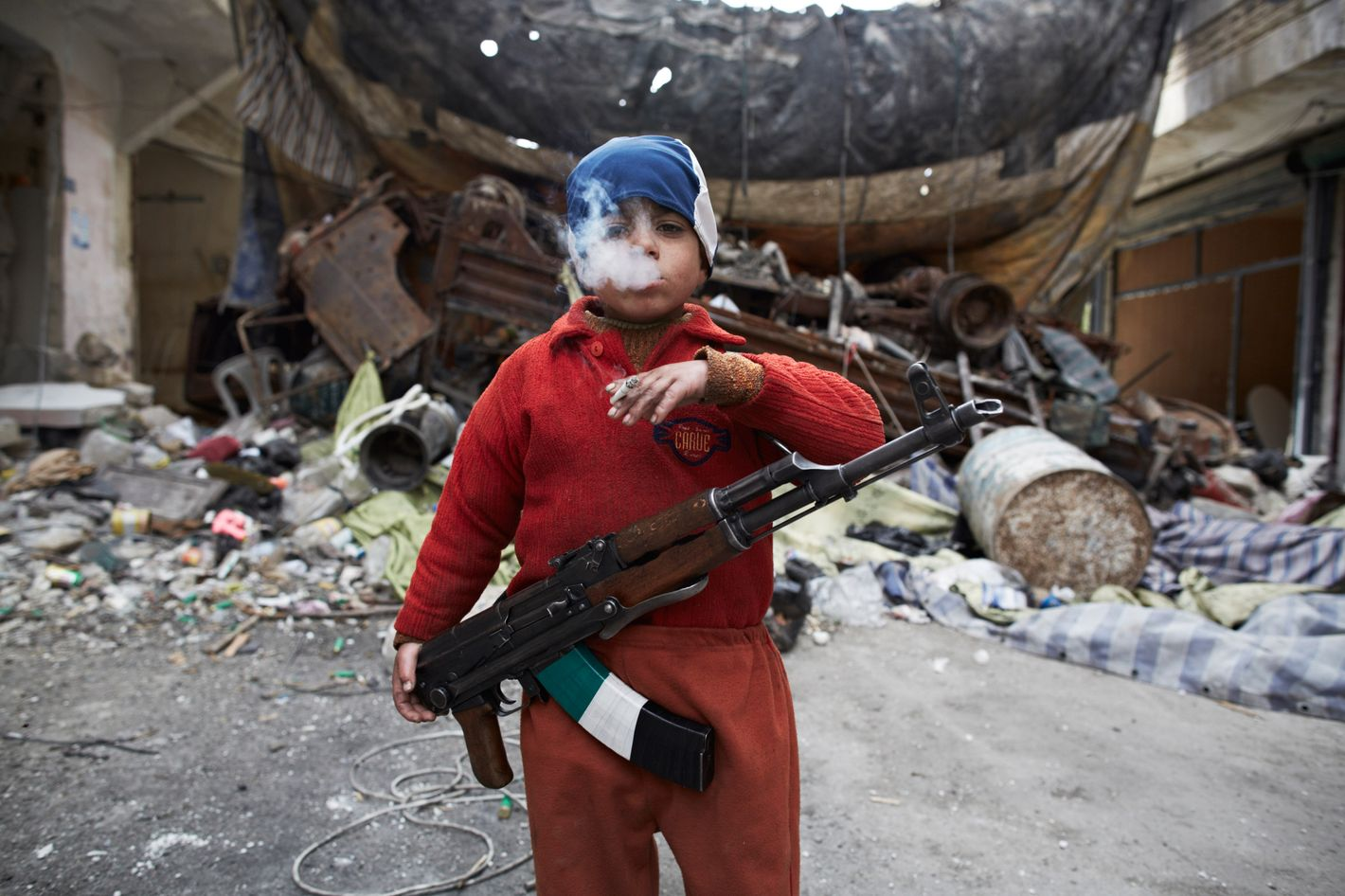 Ahmed, the 7 year old son of a FSA fighter, stands in front of a barricade, were he assits his FSA comrades in the neighborhood of Salahadeen, one of Aleppo's front lines. Aleppo, Syria, on March 27, 2013.