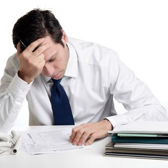 Depressed businessman doing taxes.