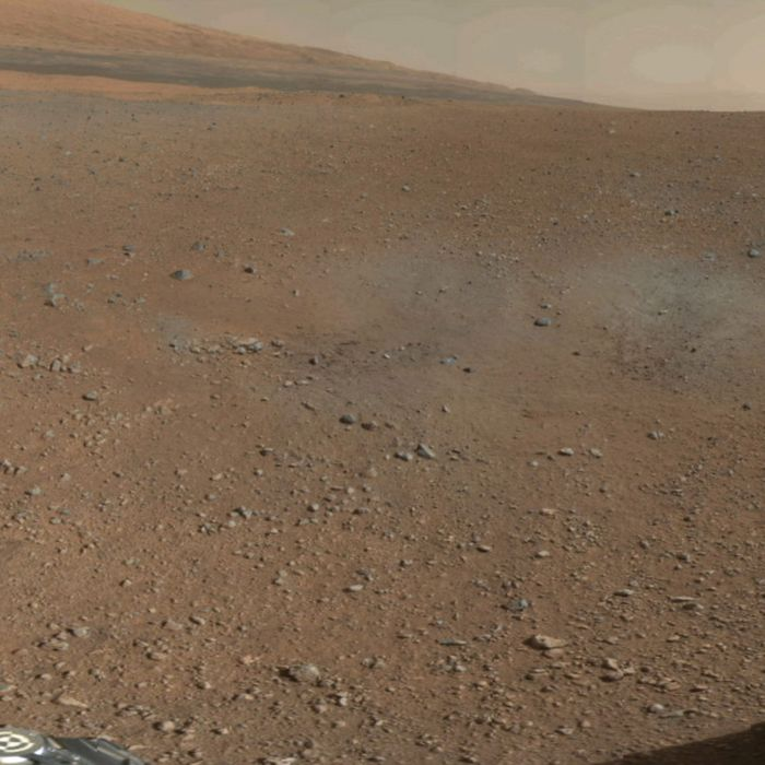 In this handout image provided by NASA and released on August 9, 2012, a color image from NASA's Curiosity Rover shows the pebble-covered surface of Mars. This is a portion of the first color 360-degree panorama from NASA's Curiosity rover, made up of thumbnails, which are small copies of higher-resolution images. The mission's destination, a mountain at the center of Gale Crater called Mount Sharp, can be seen in the distance, to the left, beginning to rise up. The mountain's summit will be imaged later. Blast marks from the rover's descent stage are in the foreground.