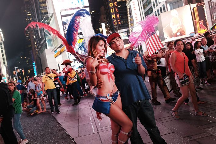Spotlight On Times Square As Painted-Topless Women Draw Ire Of Mayor And Governor