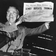 Victorious presidential candidate Pres. Harry Truman jubilantly displaying erroneous CHICAGO DAILY TRIBUNE w. headline DEWEY DEFEATS TRUMAN which overconfident Republican editors had rushed to print on election night, standing on his campaign train platform.