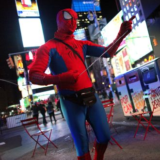 A man costumed as Spiderman chats with Gregg Deal as he walks around Times Square in Manhattan, NY, dressed in Native American garb on November 05, 2013. Deal is an American Indian street artist living in the Washington, DC area, who has undertaken projects that use stereotypes to discover how others view and interact with Native American culture.