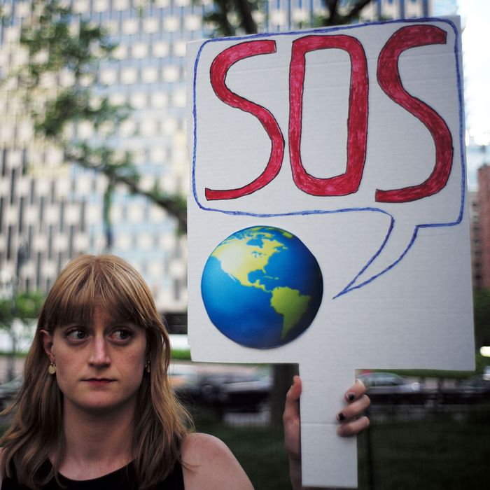 A woman displays a placard during a demonstration in New York on June 1, 2017, to protest US President Donald Trump's decision to pull out of the Paris climate accord deal.