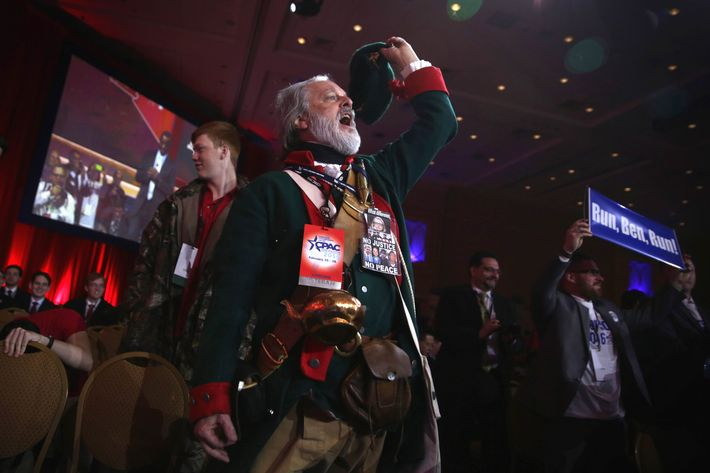 William Temple of the Golden Isles Tea Party in Georgia, dressed as Button Gwinnett, the second signer on the United States Declaration of Independence, cheers as Ben Carson speaks during the 42nd annual Conservative Political Action Conference (CPAC) February 26, 2015 in National Harbor, Maryland.